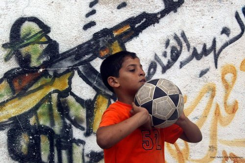 Palestinian boy plays ball next to a mural in Rafah refugee camp in Gaza on 25 June 2009 [Abed Rahim Khatib/Apaimages]