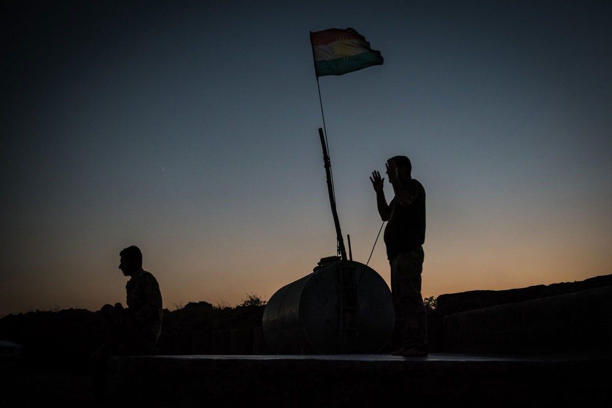 BASHIQA FRONTLINE IRAQ, AUGUST 7: Kurdish Peshmerga fighters during evening prayers on the fImage of Kurdish Peshmerga fighters [Alex Kühni]
