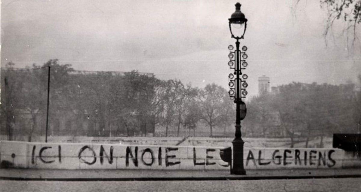 """Here we drown Algerians"" sign on Saint-Michel Bridge in Paris in 1961. Dozens of bodies were later pulled from the River Seine. [Wikipedia]"