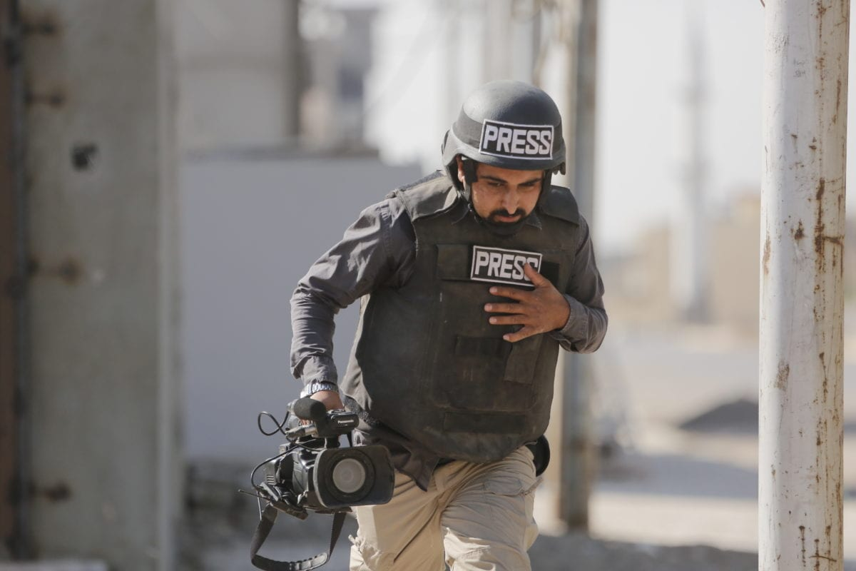 Anadolu Agency (AA) cameraman Ihsan Muhammed runs away as an armed attack is staged on a vehicle containing an AA team entering the region where suicide bombers and snipers belonging to terror group Daesh began an attack on October 21, 2016 [Yunus Keleş/Anadolu Agency]