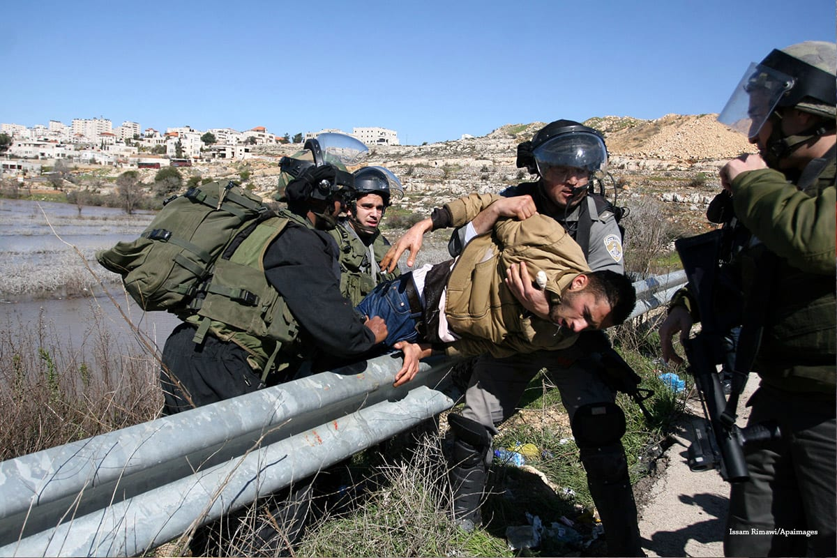 Israeli soldiers detain a Palestinian at the entrance of Ofer Prison near Ramallah [Issam Rimawi/Apaimages]