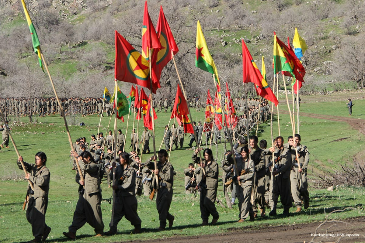 Kurdish PKK marching with their flags [KurdishstruggleWikipedia]