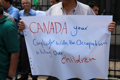 Palestinians carry banners during a protest against the policy of Canada in front of the Canadian Embassy in the West Bank on 14th August 2014 [Shadi Hatem/Apaimages]