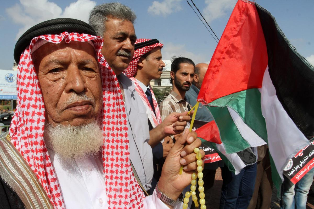 A group of Palestinian hold placards and flags during a protest marching the 99th anniversary of the Balfour Declaration at Marterys' Square in Gaza on November 01, 2016. [Abed Rahim Khatib/Anadolu Agency]