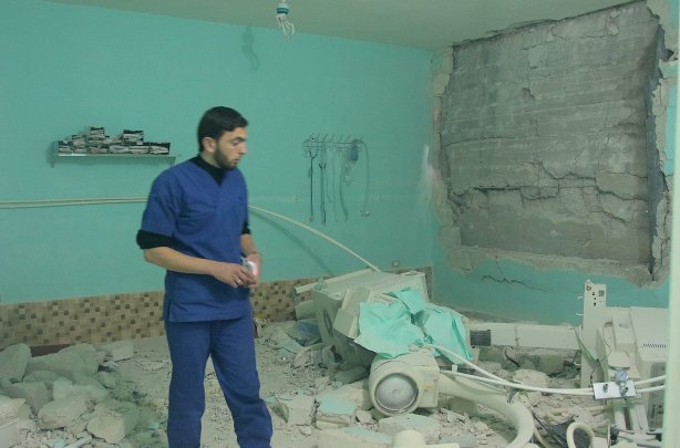 IDLIB, SYRIA - OCTOBER 13: A Syrian inspects the damage at a building after an airstrike hit a medical center in Binnis district of Idlib Syria on October 13, 2016. ( Firas Faham - Anadolu Agency )