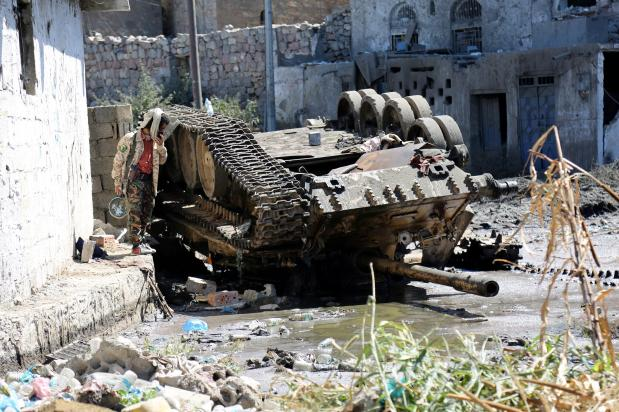 Image of a army tank turned upside down due to the violent clashes in Taiz on November 15th 2016 [Abdulnasser Alseddik/Anadolu Agency]