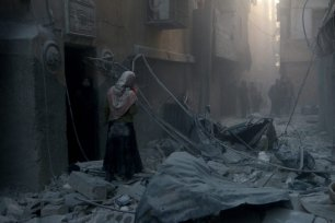 Syrian woman walks among the scene of the air strikes that were carried out by Syria and Russia in Aleppo, Syria on 21 November 2016 [Jawad al Rifai/Anadolu Agency]
