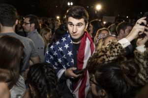 WASHINGTON, USA: A man wears an American Flag around his shoulders in a crowd of Clinton and Trump supporters that has gather in front of the White House as the results of the 2016 Presidential Election became clear in Washington, USA on 9 November 2016. [Samuel Corum/Anadolu Agency]