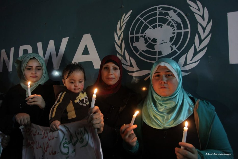 Syrian refugees and Palestinian-Syrian hold banners and candles in solidarity with people who are living in Yarmouk Palestinian refugee camp in Syria, on December 29 2013 [Ashraf Amra/Apaimages]