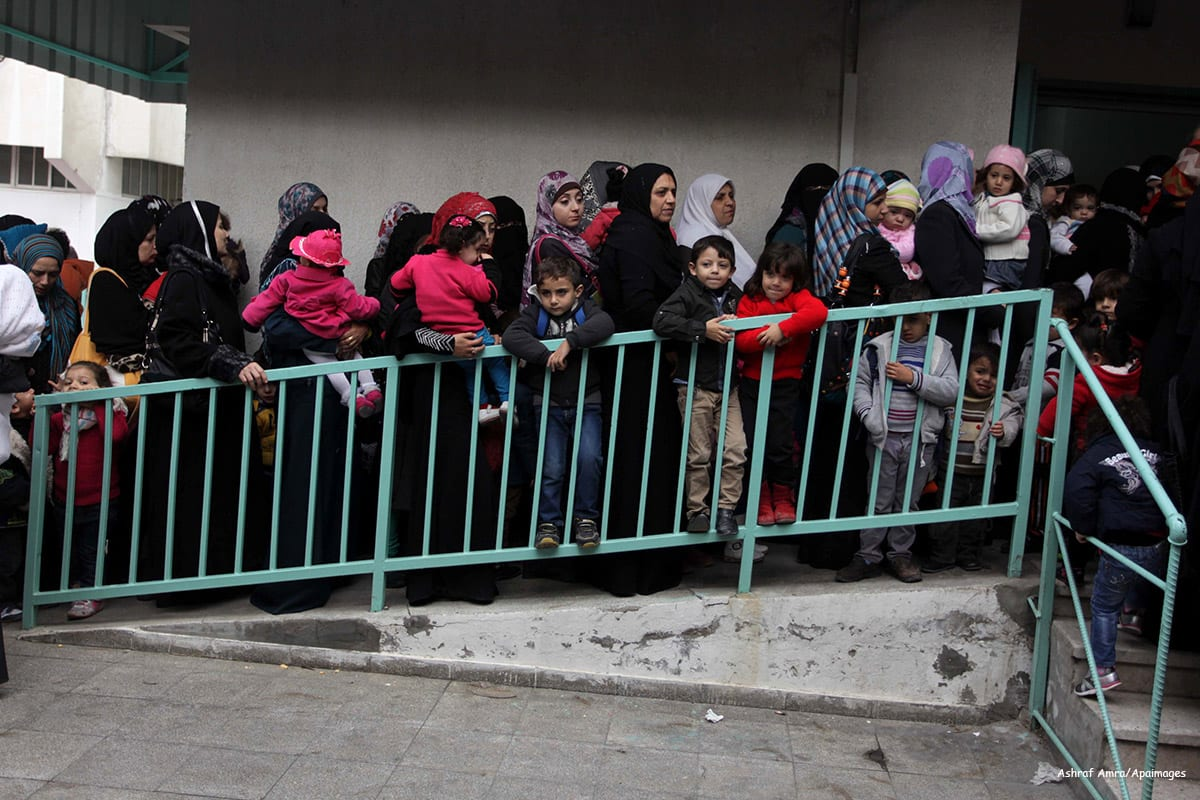 Palestinians wait in line to receive health care in Gaza on December 9 2013 [Ashraf Amra/Apaimages]