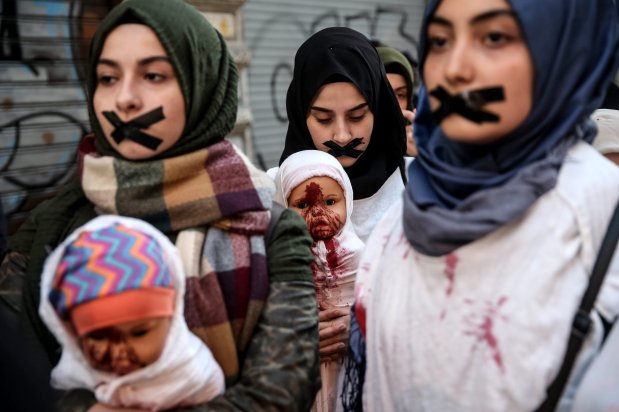 ISTANBUL, TURKEY - DECEMBER 08: Protesters with their mouths taped with black tapes stage a show with red painted shrouded dolls, symbolizing murdered children and babies during a demonstration, condemning massacres and attacks in Syria's Aleppo over civilians within the on going civil war, on December 08, 2016 in front of the Galatasaray High School at the Istiklal Street in Istanbul, Turkey. ( Berk Özkan - Anadolu Agency )