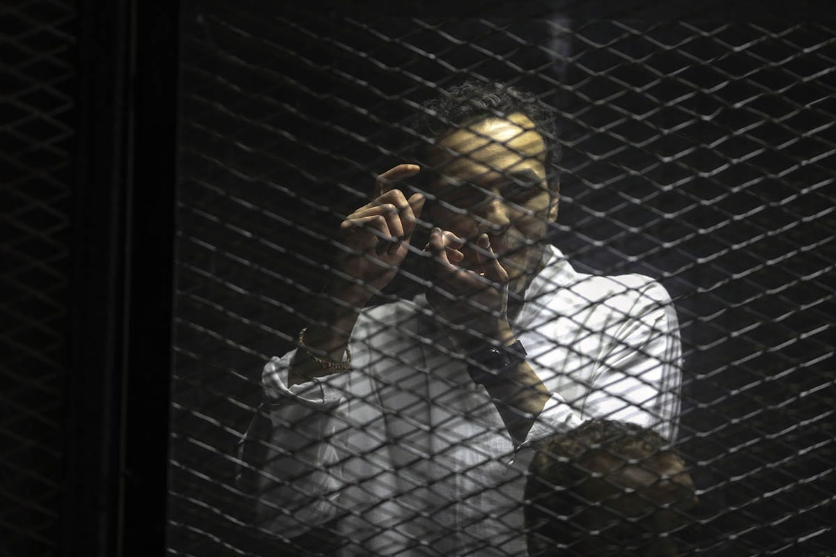 Journalist Mohammad Shukan is seen behind the cage during the trial over the breaking up the Rabaa Al-Adawiyyah protests, at the police academy in Cairo, Egypt on December 10, 2016 [Moustafa Elshemy / Anadolu Agency]