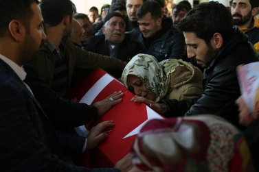 Relatives of police officer Suleyman Sorkut, who was martyred during Istanbul terror attacks, mourn over the coffin during the funeral ceremony in Siverek district of Sanliurfa, Turkey on December 11, 2016 [ Mehmet Fatih Aslan / Anadolu Agency]