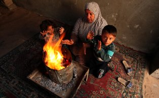 GAZA CITY, GAZA - DECEMBER 14: A woman and children try to warm up sitting near a heating stove as cold weather affects Khan Yunis in Gaza on December 14, 2016. ( Ashraf Amra - Anadolu Agency )