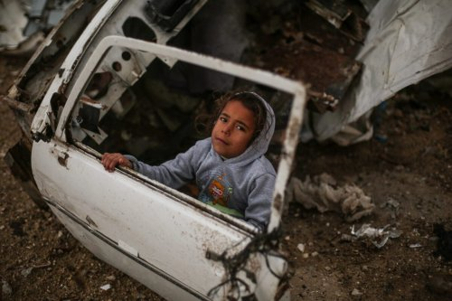 A Palestinian child is seen near a car wreck as Palestinians living in makeshift homes in El-Zohor neighbourhood in the city of Khan Yunis on the Gaza Strip are facing difficult conditions under the cold weather on December 14, 2016 [Mustafa Hassona / Anadolu Agency]