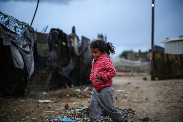 Palestinian children play outside as Palestinians living in makeshift homes in El-Zohor neighborhood in the city of Khan Yunis on the Gaza Strip are facing difficult conditions under the cold weather on December 14, 2016. The economy and their living conditions are getting progressively worse due to Israel's embargo on Gaza. ( Mustafa Hassona - Anadolu Agency )