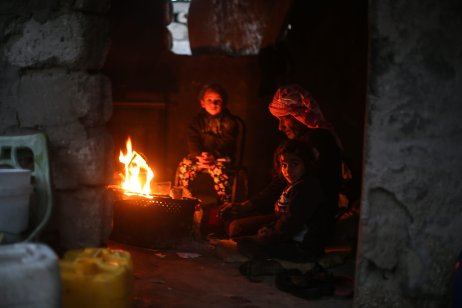 Palestinian children huddle by the fire inside a makeshift home as living conditions deteriorate in Gaza (Mustafa Hassona/Anadolu Agency)