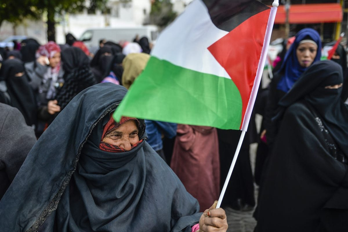 A Palestinian woman carries the Palestinian flag during a workers' protest against Israeli blockade of Gaza, in Gaza City, Gaza on December 27, 2016. ( Mustafa Hassona - Anadolu Agency )