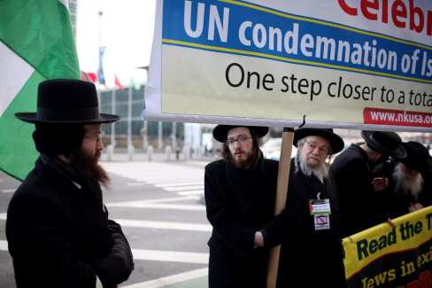 NEW YORK, UNITED STATES - DECEMBER 28: Members of Orthodox Jews hold banners during a protest to celebrate UN decision to condemn Israeli settlements outside the United Nations headquarters in Manhattan borough of New York City, USA on December 28, 2016. ( Mohammed Elshamy - Anadolu Agency )