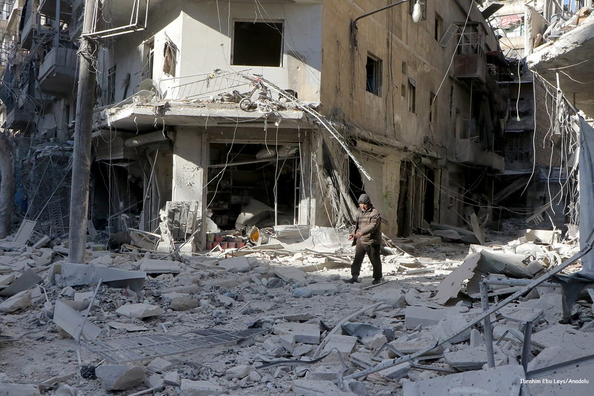 Image of a man walking past the buildings that Assad Regime forces attacked in Aleppo, Syria on December 6 2016 [İbrahim Ebu Leys/Anadolu]