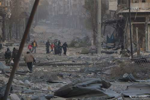 Civilians walk in ruined buildings and streets after the Assad regime carried out airstrikes in Aleppo, Syria on December 9 2016 [Ibrahim Ebu Leys/Anadolu]