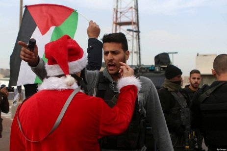 A Palestinian protester dressed up as Santa Claus argues with an Israeli border guard during clashes at a demonstration next to a section of Israel's separation wall in the biblical town of Bethlehem, in the occupied West Bank, on December 23, 2016 [Shadi Hatem/ApaImages]