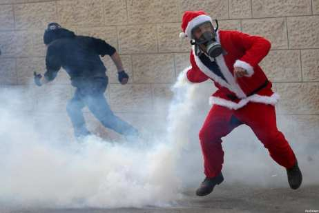 A Palestinian man dressed up as Santa Claus throws back a tear gas grenade fired by Israeli border guard during clashes at a demonstration next to a section of Israel's separation wall in the biblical town of Bethlehem, in the occupied West Bank, on December 23, 2016 [Shadi Hatem/ApaImages]
