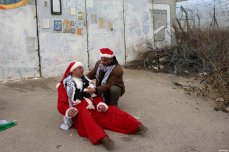 A man tends to a Palestinian protester, dressed as Santa Claus, after inhaling tear gas fired by Israeli border guard during clashes at a demonstration next to a section of Israel's separation wall in the biblical town of Bethlehem, in the occupied West Bank, on December 23, 2016 [Shadi Hatem/ApaImages]
