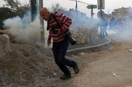 A Palestinian Photographer takes cover form a tear gas grenade fired by Israeli border guard during clashes at a demonstration next to a section of Israel's separation wall in the biblical town of Bethlehem, in the occupied West Bank, on December 23, 2016 [Shadi Hatem/ApaImages]