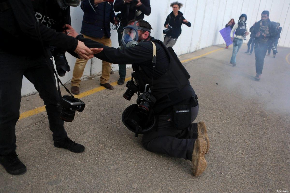 Un photographe palestinien est évacué après avoir inhalé une grenade lacrymogène tirée par la garde de la frontière israélienne lors d'affrontements lors d'une manifestation à côté d'une section du mur de séparation d'Israël dans la ville biblique de Bethléem, en Cisjordanie occupée, le 23 Décembre, 2016 [Shadi Hatem / ApaImages ]