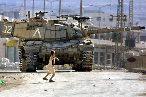 A Palestinian child throws stones at an Israeli Defence Force's tank, much like the iconic image of Faris Odeh from October 2000, during the First Intifada [Musa Al-Shaer / AFP]