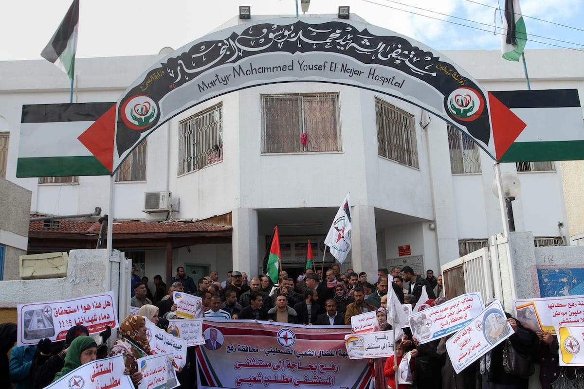 A group of protesters hold banners during a demonstration demanding opening of a new hospital in Rafah, Gaza on January 3, 2017 [Abed Rahim Khatib/ Anadolu Agency]