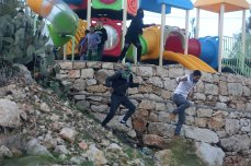 RAMALLAH, WEST BANK - JANUARY 4: Palestinians throw stones back to Israeli forces as they try to demolish a building that the building were unlicensed in Bedres town of Ramallah, West Bank on January 4, 2017 ( Issam Rimawi - Anadolu Agency )