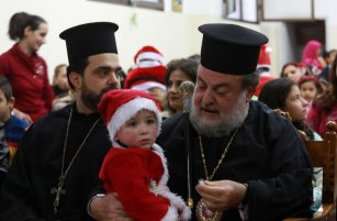 Archbishop Alexios (R) attends a celebration within Christmas preparations [Mohammed Asad/Anadolu Agency]