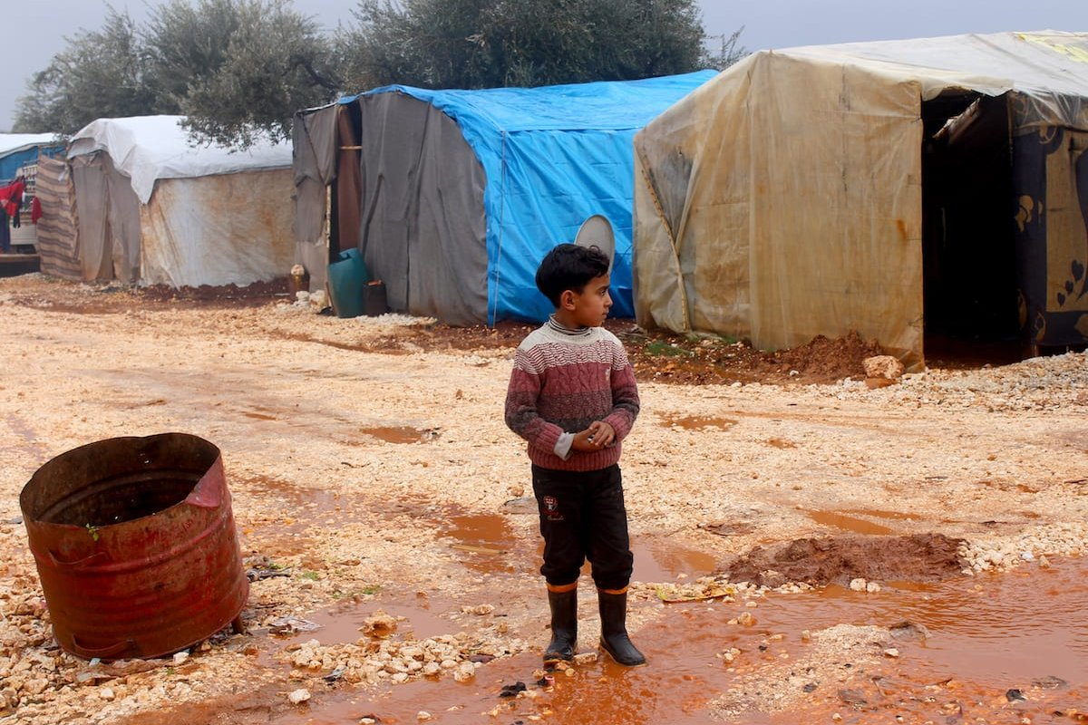 A Syrian child walks over a muddy road between tents at the Refugee camp in Idlib, Syria on January 9 2017 [Abdulghani Arian/Anadolu Agency]