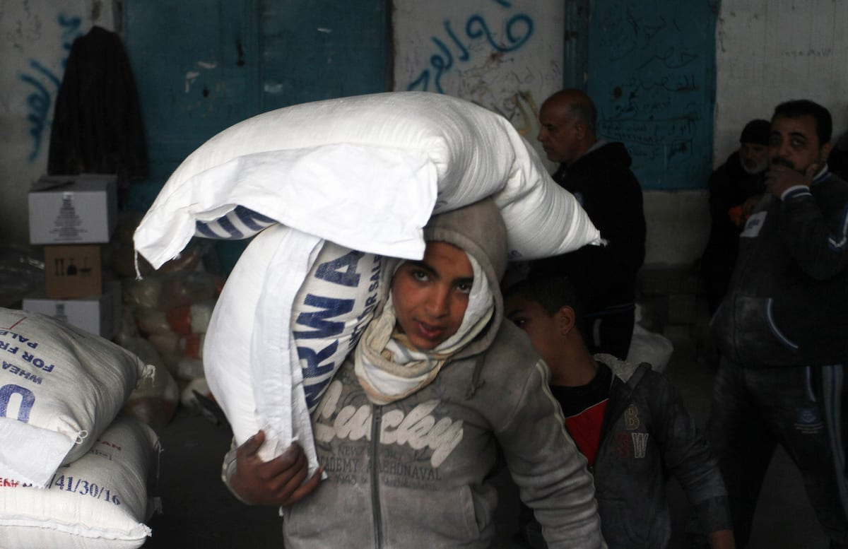 A Palestinian child carries sacks of flours during a food aid distribution by the United Nations Relief and Works Agency in Rafah, Gaza on January 22, 2017. ( Abed Rahim Khatib - Anadolu Agency )