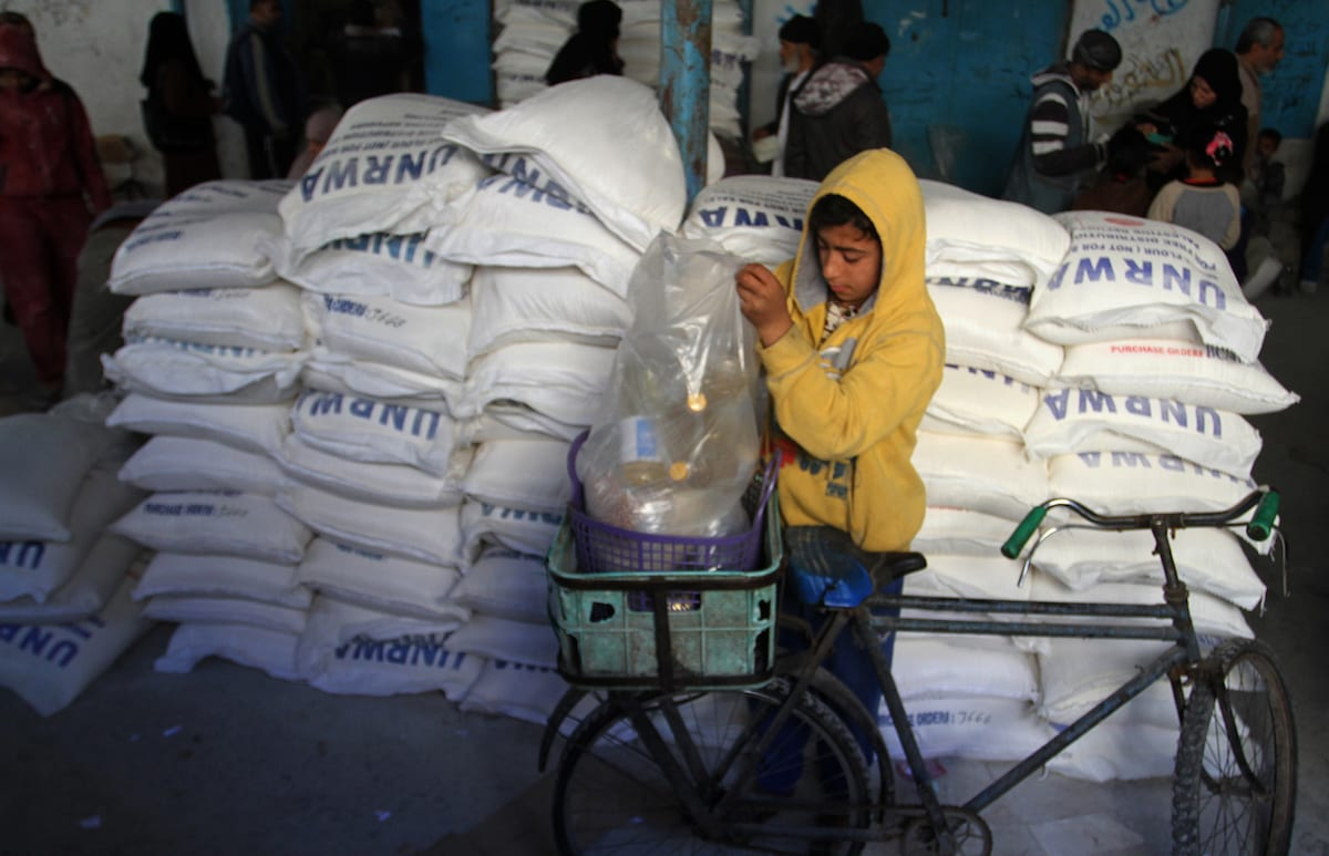 A Palestinian child loads provisions on his bicycle's rear basket during a food aid distribution by UNRWA in Rafah, Gaza on January 22, 2017 [Abed Rahim Khatib / Anadolu Agency]