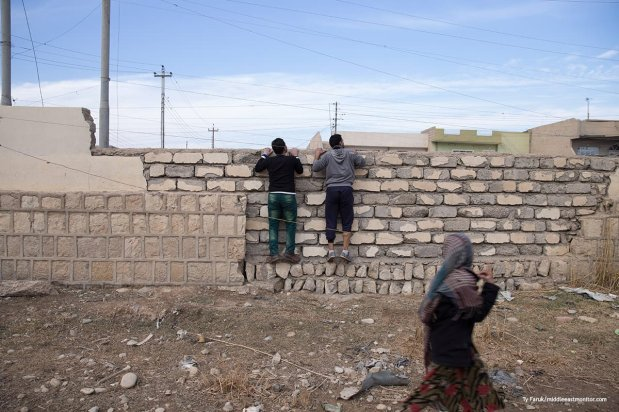 Two men look over a wall in Mosul hoping to help their friends jump the queue into a distribution centre before shots are heard and they abandon their plan [Ty Faruk/middleeastmonitor.com]