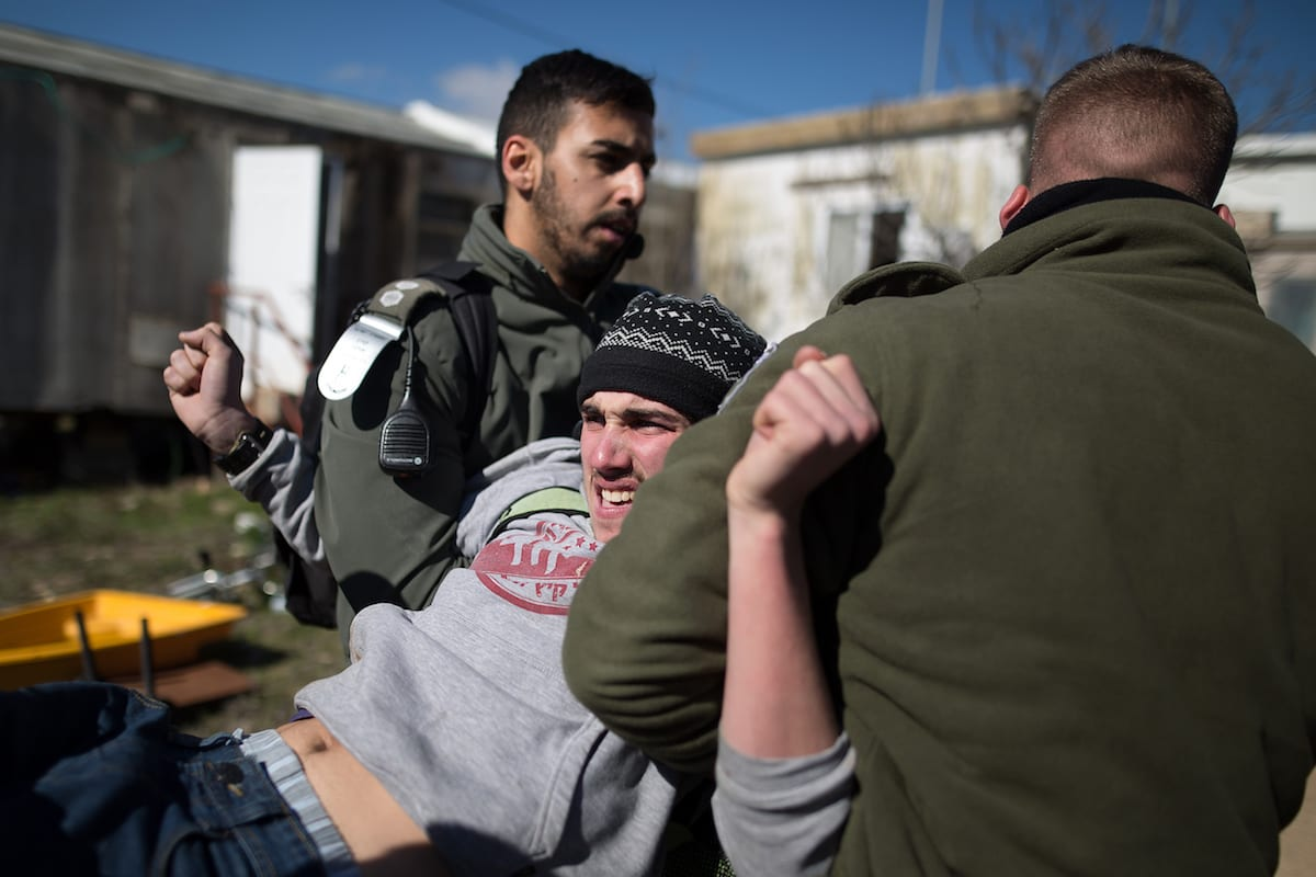 Jewish settlers who reject to leave the settlement, prepare for a possible police intervention as they gather around a synagogue despite the police officers evacuation of the Jewish settlement of Amona north east of Ramallah, West Bank on February 2, 2017 [Ilan Assayag - Anadolu Agency]