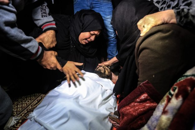 RAFAH, GAZA - FEBRUARY 09: (EDITORS NOTE: Image depicts death.) Palestinians mourn around the body of Muhammed Enver el-Akra (38), who was killed by Israeli forces, during a funeral ceremony in Rafah, Gaza on February 09, 2017. His dead body was brought from the Abu Yusuf Necar Hospital's morgue to his home in Sheikh Ridvan district of Gaza. ( Ali Jadallah - Anadolu Agency )