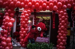 GAZA CITY, GAZA - FEBRUARY 14: A boy carries a red bear in front of a decorated souvenir gift shop on Valentine's Day in Gaza City, Gaza on February 14, 2017. ( Ali Jadallah - Anadolu Agency )