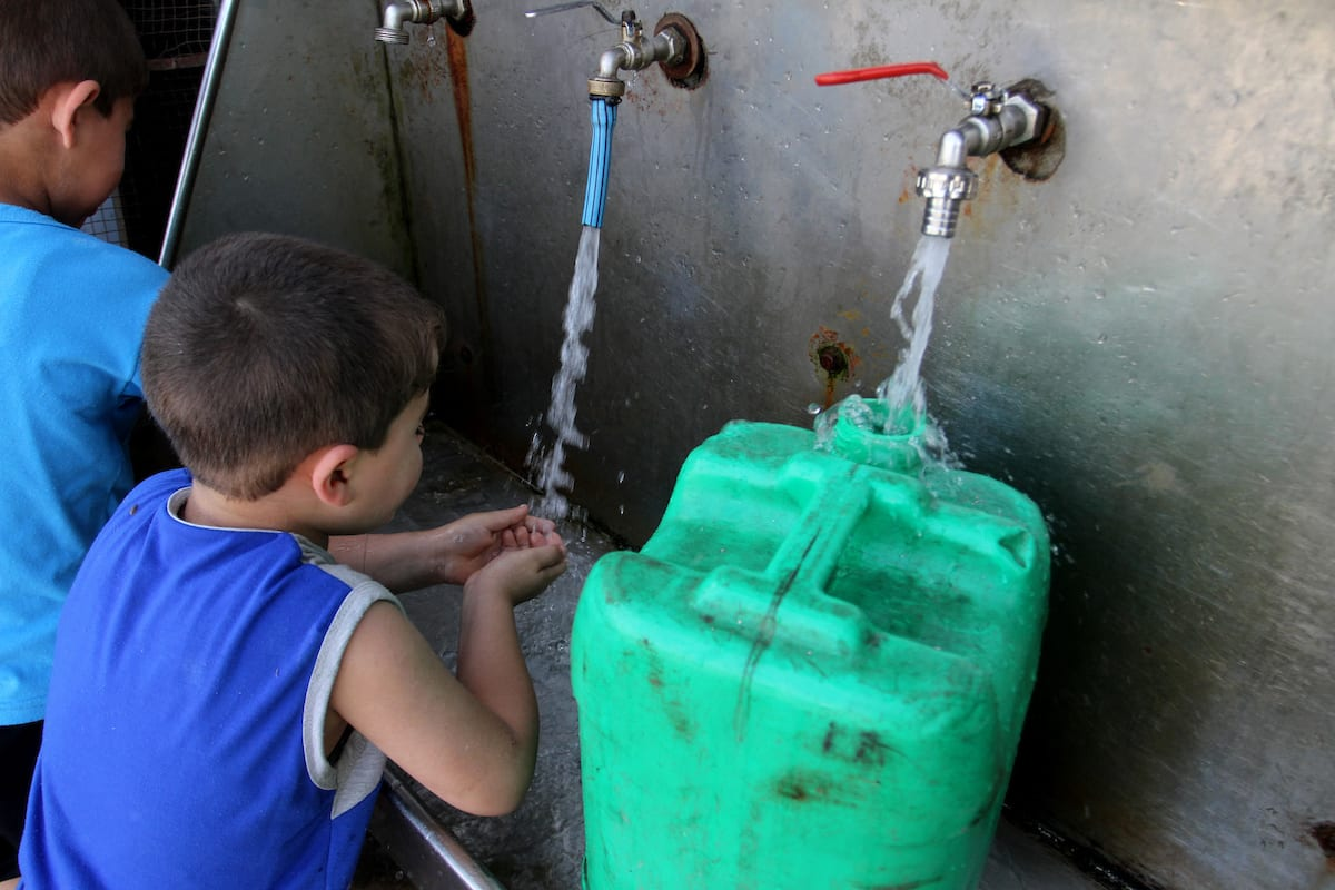 Palestinian boys drink a water from a public tap in Rafah in the southern Gaza strip, on May 22, 2016 [Abed Rahim Khatib/Apa Images]