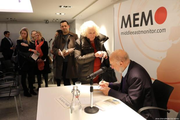 Former United Nations Special Rapporteur for Palestine Richard Falk signs copies of his new book at an event hosted by MEMO on 20 March 2017 [Jehan AlFarra/Middle East Monitor]
