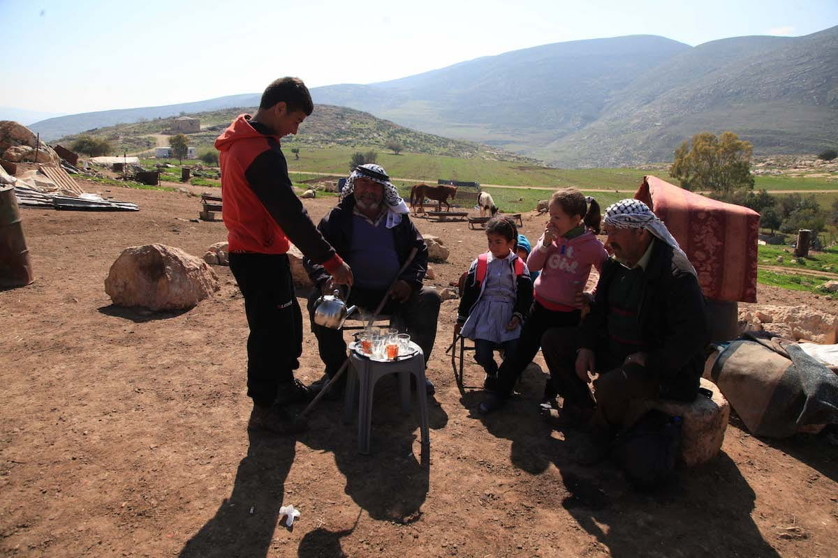 A Palestinian family gather to drink tea near their caves using as a home after their sheds were demolished by Israeli bulldozers on 3rd January, on the grounds that their scrap metal sheds were unlicensed, in Harbetu Tana village of Nablus, West Bank on February 27, 2017. Most of the Palestinian families forced to move into caves and try to live in hard conditions and primitively [Issam Rimawi / Anadolu Agency]
