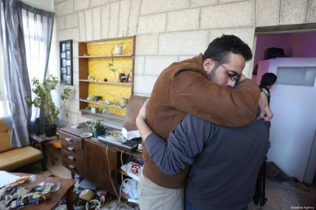 RAMALLAH, WEST BANK - MARCH 6: Men hug each other in Basil Al-Araj's house after Israeli soldiers stormed into and open fire on Basil Al-Araj's house, 31, in Ramallah, West Bank on March 6, 2017. After Israeli forces stormed into Israeli's houses Basil Al-Araj killed and 2 others injured. ( Issam Rimawi - Anadolu Agency )