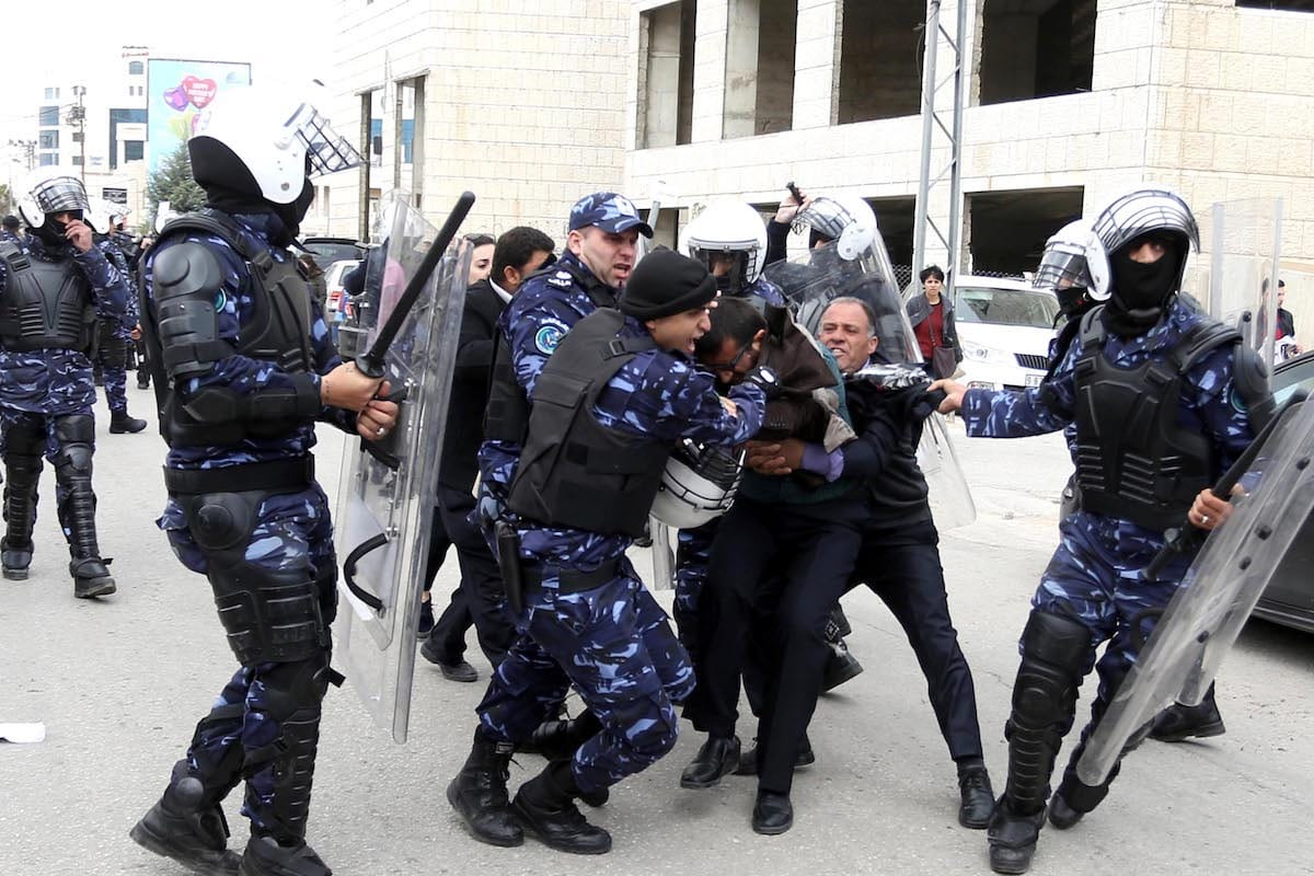 Image of the Palestinian Authority police forces violently intervening a protest against the trial of Basel al-Araj, who was killed during a raid by Israeli soldiers at his home, and his five friends in front of the Ramallah Minor Court in Ramallah, West Bank, March 12, 2017 ( Issam Rimawi - Anadolu Agency )