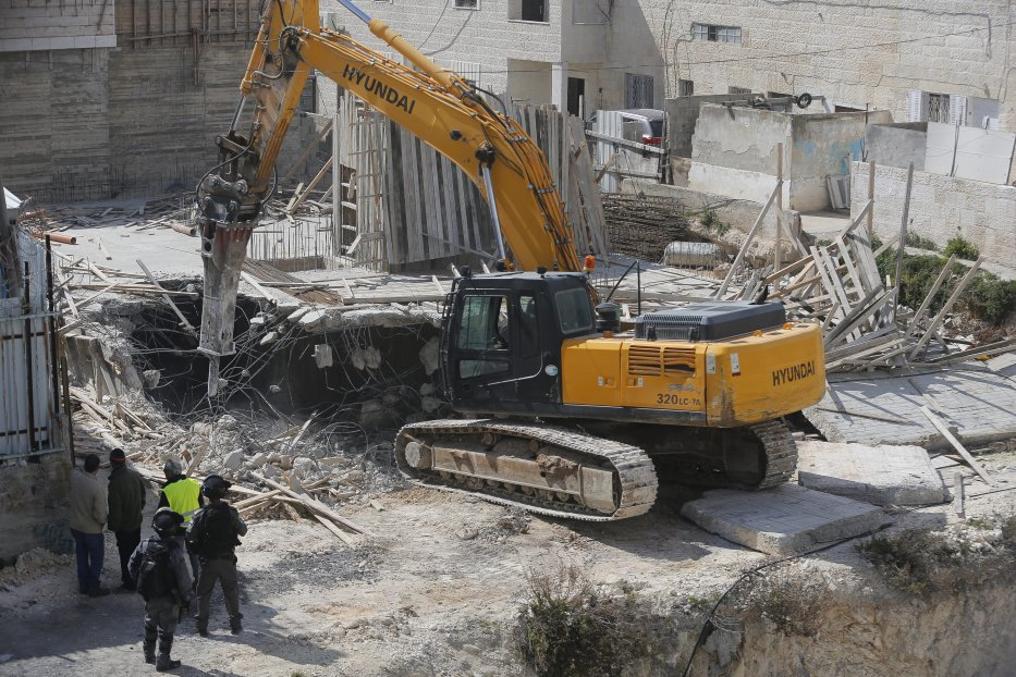 Israeli security forces gather around a construction site as the demolition of a Palestinian home is about to take place in Jerusalem on 14 March 2017 [Mostafa Alkharouf/Anadolu Agency]