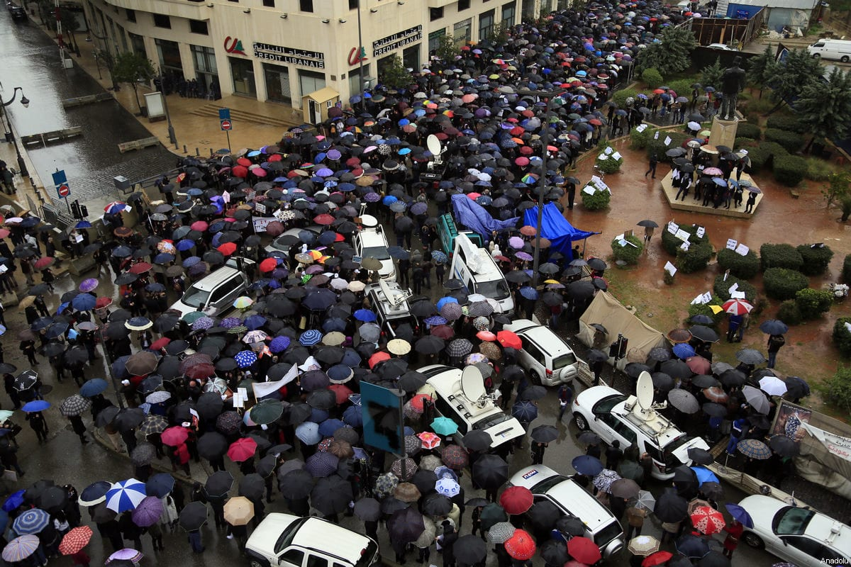 High school and primary school teachers holding umbrellas stage a demonstration demanding a wage increase at Riad Al Solh Square as the government holds a meeting on budget in Beirut, Lebanon on March 15, 2017 [ Ratib Al Safadi / Anadolu Agency