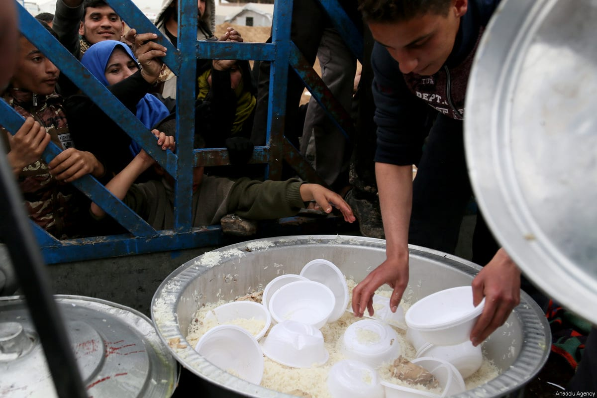 Iraqi civilians queue to collect food at the refugee camp in Hamam Ali town, Iraq on 19 March 2017 [Yunus Keleş/Anadolu Agency]
