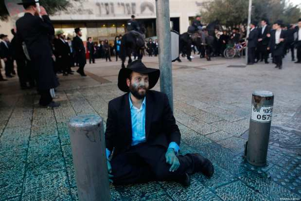 JERUSALEM: An Ultra Orthodox Jew sits on the pavement during a protest against the compulsory military service on 20 March 2017. [Gil Cohen Magen/Anadolu Agency]